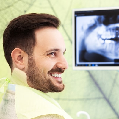 Male patient looking at his digital x-rays in our dental office