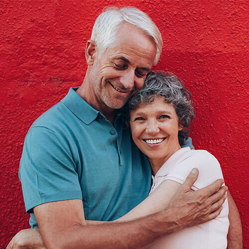 Older couple smiling and hugging after their Woburn services, which included an oral cancer screening